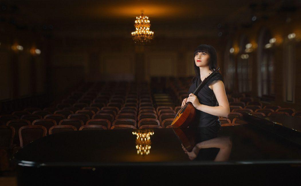 Кристина Шарабидзе стоит с домрой в концертном зале